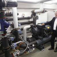 Robert Simmer, director of municipal services in Amstetten, Austria, poses May 7 with a heat pump that extracts energy from the town sewer. | AFP-JIJI