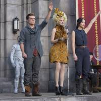 Josh Hutcherson (left), Elizabeth Banks (center) and Jennifer Lawrence are seen in a still from 'The Hunger Games: Catching Fire.' A three-fingered gesture used by characters in the film has been adopted by Thai anti-coup demonstrators as a symbol of resistance in Bangkok. | AP