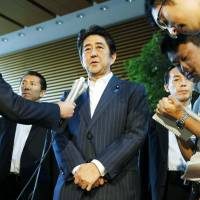Prime Minister Shinzo Abe announces his decision Friday to push for a lower corporate tax rate. | KYODO