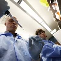 Jaime Wendt and Mike Tschannen work to sequence genes on May 9 at the Medical College of Wisconsin in Milwaukee. | REUTERS