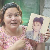 Beirut Calaguas holds up a photo of herself when she was 17 years old during an interview at the end of May in Angeles. | AFP-JIJI