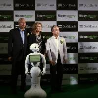 Former U.S. Secretary of State Colin Powell, now an external board member of Bloom Energy, appears in Tokyo on Tuesday with U.S. Ambassador Caroline Kennedy and SoftBank Corp. Chief Executive Masayoshi Son to launch Bloom Energy Server, a solid-oxide fuel cell that its manufacturer says produces clean energy. With them is SoftBank's Pepper robot. | REUTERS