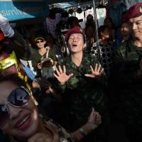Thai soldiers dance with residents at a military event organized to 'return happiness to the people' at Bangkok's Victory Monument, the site of recent anti-coup rallies, on Wednesday.   AFP-JIJI