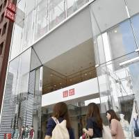 Women walk outside the Uniqlo store in Tokyo's upscale Ginza district on Tuesday. | KYODO