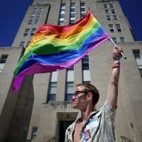 Gary Jones, 37, holds a rainbow-striped gay and lesbian pride flag in front of Racine County Courthouse during a march in Racine, Wisconsin, on Friday.   AP