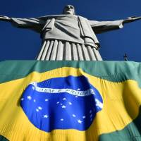 A Brazilian flag covers the base of the 'Christ the Redeemer' statue in Rio de Janeiro on Thursday.   AFP-JIJI