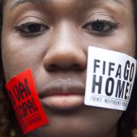 A woman protests during a demonstration against the 2014 World Cup on Rio de Janeiro's Copacabana Beach on Thursday.   AP