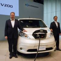Andy Palmer, chief planning officer and executive vice president of Nissan Motor Co., and Takao Katagiri, another executive vice president, present the e-NV200 electric van in Yokohama on Monday ahead of its launch in Europe this month and in Japan in October. | KYODO