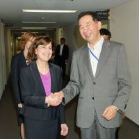 Hiroshi Oe, Japan's deputy chief negotiator for the Trans-Pacific Partnership free trade talks, shakes hands with acting Deputy U.S. Trade Representative Wendy Cutler before their meeting in Tokyo on Monday. | KYODO