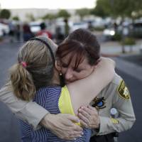 A woman embraces a Las Vegas Metropolitan Police officer on Monday after a vigil near CiCi's Pizza in Las Vegas, where two police officers were shot dead a day earlier. | AP