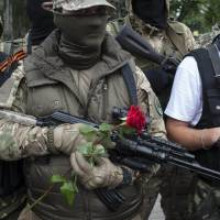 Pro-Russian fighters hold flowers after taking the oath of allegiance to the self-proclaimed 'Donetsk People's Republic' in Donetsk, Ukraine, on Saturday. | AP
