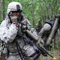 A U.S. soldier (left) takes part in a training exercise during the first phase of Saber Strike 2014, at Rukla military base in Lithuania, on June 14. Saber Strike, a NATO exercise, took place over multiple locations in Latvia, Lithuania and Estonia, and involved approximately 4,700 personnel from 10 countries from the U.S. and ex-Soviet Baltic states amid a spike in tensions with Moscow over the Ukraine crisis.   AFP-JIJI