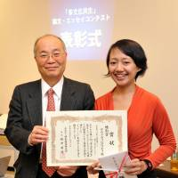 First steps: At an event in January 2013, former Tokyo Immigration Bureau chief Hidenori Sakanaka presents Indonesian Dewi Rachmawati with a prize for an essay she wrote about her struggle to become a nurse in Japan. | YOSHIAKI MIURA