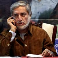Afghan presidential candidate Abdullah Abdullah talks on the phone during a campaign rally shortly after his convoy was attacked in Kabul on Friday. The Afghan Interior Ministry said a suicide bomber and a roadside bomb struck Abdullah's convoy as it left an earlier campaign event at a wedding hall in the capital, killing several civilians but leaving the candidate himself unharmed. | AP