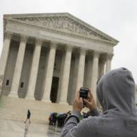 A man takes a photo of the Supreme Court with his cellphone in Washington on April 29. | AP