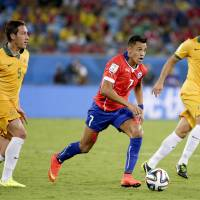 Bob and weave: Chile's Alexis Sanchez (center) runs between Australia's Mark Milligan (left) and Mark Bresciano during their group B match at the 2014 World Cup in Cuiaba, Brazil. | AFP-JIJI