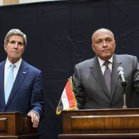 U.S. Secretary of State John Kerry and Egyptian Foreign Minister Sameh Shoukri listen to a question during a joint news conference in Cairo on Sunday. | REUTERS