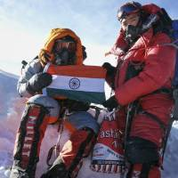 Malavath Poorna (left) holds up India's national flag on the summit of Mount Everest on May 25. Poorna said she ascended the mountain with a team of Nepalese Sherpas from the northern side in Tibet. | AP