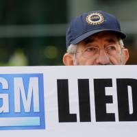 A protester pickets General Motors headquarters during the carmaker's annual meeting in Detroit on June 10. The troubled automaker announced another recall Monday, its 44th this year, over problems linked the ignition switches. | BLOOMBERG