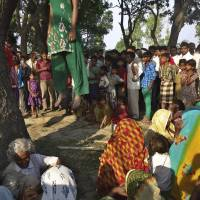 Villagers gather around the bodies of two girls found murdered and hanging from a tree in Uttar Pradesh, India, after they were allegedly gang-raped by four local men, two of whom are police officers. | AP