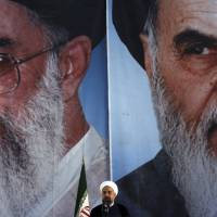 Iranian President Hassan Rouhani delivers an address in front of portraits of Supreme Leader Ayatollah Ali Khamenei (left) and Ayatollah Khomeini, the founder of the Islamic Republic, during a ceremony marking the anniversary of Khomeini's death at his shrine just outside Tehran on Tuesday. | AP