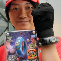 Tomy's Pokemon Mega Ring is seen being demonstrated Tuesday. | SATOKO KAWASAKI