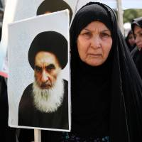 An Iraqi woman living in Iran holds a poster of Grand Ayatollah Ali al-Sistani, Iraq's top Shiite cleric, during a demonstration against Sunni militants from the Islamic State of Iraq and the Levant in Tehran on June 20. | AP