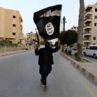 A member of the Islamic State of Iraq and the Levant (ISIL) waves the group's flag in Raqqa, Syria, on Sunday. The group, which has captured vast tracts of territory in Iraq and Syria, has declared itself an Islamic caliphate and called on factions worldwide to unite behind its leader, Abu Bakr al-Baghadi.   REUTERS