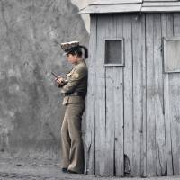 A North Korean soldier uses her mobile phone next to a sentry post on the banks of the Yalu River, opposite the Chinese border city of Dandong on June 1. Chief Cabinet Secretary Yoshihide Suga announced Sunday that the government has submitted a list of about 470 Japanese citizens who may have been kidnapped by North Korea in the 1970s and '80s. | REUTERS