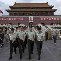 Paramilitary policemen march out of Tiananmen Gate to clear tourists from the area for a May 28 flag-lowering ceremony at Tiananmen Square in Beijing. | AP
