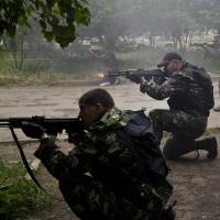 Pro-Russian rebels fire their weapons during fierce clashes with Ukrainian troops on the outskirts of Luhansk, in Ukraine's east, on Monday. | AP