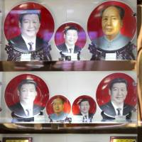 A vendor sells commemorative plates with images of Chinese President Xi Jinping and late Chinese leader Mao Zedong near Tiananmen Square in Beijing on June 4. Xi's anti-graft campaign is now targeting officials who have sent their spouses and children abroad, where they can create channels to funnel illicit gains and establish footholds for an eventual escape from the mainland. | AP