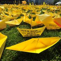 Mourners' messages are seen on origami ships laid out at a memorial for victims of the Sewol ferry disaster in Seoul on May 7. | AFP-JIJI