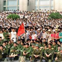 People's Liberation Army soldiers sit with protesters in front of the Great Hall of the People in Beijing's Tiananmen Square on June 3, 1989. China's vast censorship machine does its utmost to wipe the slightest reference to the Tiananmen crackdown from books, television and the Internet, scrubbing the issue from public discussion and even from the minds of its younger generation. | AFP-JIJI