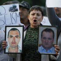 A woman holds portraits of people killed during the unrest in Ukraine as Pro-Russian demonstrators shout slogans in the eastern city of Donetsk on Monday.   AP