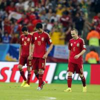 End of an era: Spanish players walk dejectedly after a goal by Chile's Charles Aranguiz in their Group B match at Maracana Stadium in Rio de Janeiro on Wednesday. Chile won 2-0.  | AP