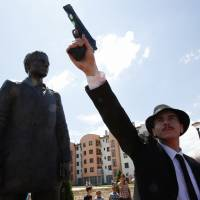 Bosnian actor Jovan Mojsilovic poses with a plastic replica gun in Sarajevo on Friday during a ceremony to unveil a statue of Gavrilo Princip, who ignited World War I by assassinating the Austro-Hungarian crown prince on June 28, 1914. | AP