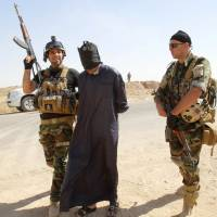 Kurdish security personnel detain a suspected militant from the Islamic State in Iraq and Syria insurgent group outside Kirkuk, Iraq, on Monday.   REUTERS