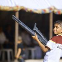 An Iraqi boy holds a weapon Tuesday as he takes part in a gathering of Shiite tribesman showing their willingness to join Iraqi security forces in the fight against ISIS jihadi militants who have taken over several cities in northern Iraq.   AFP-JIJI