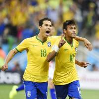 Best foot forward: Brazil's Neymar (right) celebrates with Hernanes after converting a penalty against Croatia in the opening game of the World Cup on Thursday in Sao Paulo. Brazil won 3-1. | KYODO