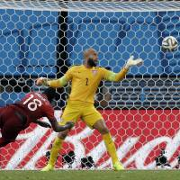 Better late than never: Portugal's Silvestre Varela heads the ball past United States goalkeeper Tim Howard during extra time on Sunday in Manaus, Brazil. The match ended 2-2 draw.   AP
