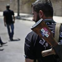 A Syrian soldier carrying an AK-47 with a sticker of Syrian President Bashar Assad and the Arabic words reading 'Syria is fine' stands guard at a checkpoint in Damascus last Aug. 21. | AP