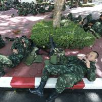 Thai soldiers rest after being deployed at police headquarters to prevent an anti-coup demonstration in Bangkok on Sunday. | AP