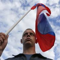 A participant attends a rally in Moscow on Wednesday in support of pro-Russian residents of Ukraine's eastern regions as well as the self-proclaimed People's Republics of Donbass and Luhansk. | REUTERS