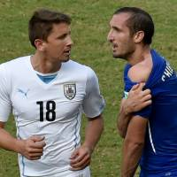 Shoulder the blame: Italy defender Giorgio Chiellini reveals an apparent bite mark left by Uruguay's Luis Suarez, as Uruguay's Gaston Ramirez (left) looks on. | AFP-JIJI