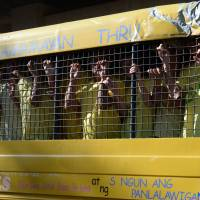 Chinese and Vietnamese fishermen arrested separately for illegal fishing arrive in a prison vehicle for their trial at a court in Puerto Princesa City, southwest of Manila, on Wednesday. | AFP-JIJI