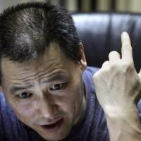 Chinese attorney Pu Zhiqiang speaks during a June 2010 interview at his office in Beijing. Police on Friday formally arrested the well-known rights lawyer. | AP