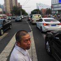 A man waits for traffic to pass at an intersection in Beijing on Thursday. The majority of rumors swirling in the capital target government officials and the rich, state-run media said on Wednesday, underscoring popular resentment at China's privileged amidst deepening inequality. | AFP-JIJI