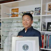 Charlie Furusho, who has flown with 156 different airlines, holds a certificate from Guinness World Records recognizing his accomplishment at his home in Narita, Chiba Prefecture, in late May. | KYODO