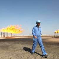 An engineer walking past chimneys at the Barjisiya oil fields southwest of the city of Basra, Iraq. Escalating violence in Iraq prompted the evacuations of more than 1,200 Chinese workers who had been trapped in the embattled northern Iraqi city of Samarra, the official Xinhua News Agency said Saturday. | AFP-JIJI